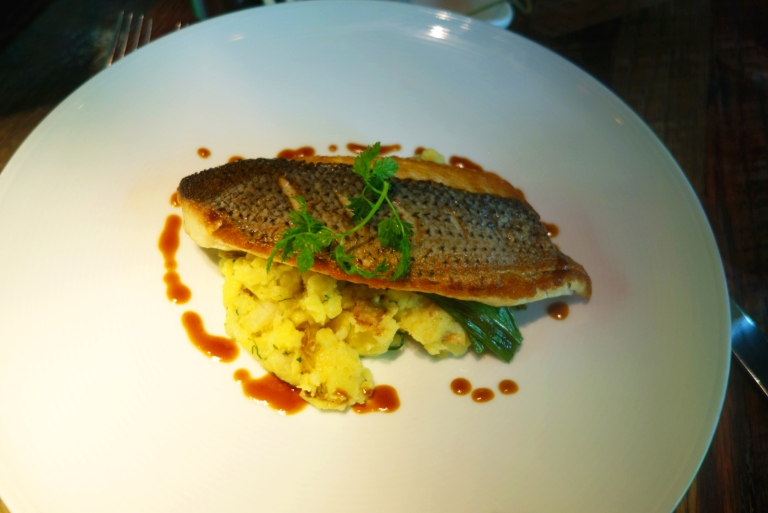 Urbo Kitchens, Urbo - Times Square - Pan Roasted Striped Bass with crushed butterball potatoes, grilled scallions & truffle butter