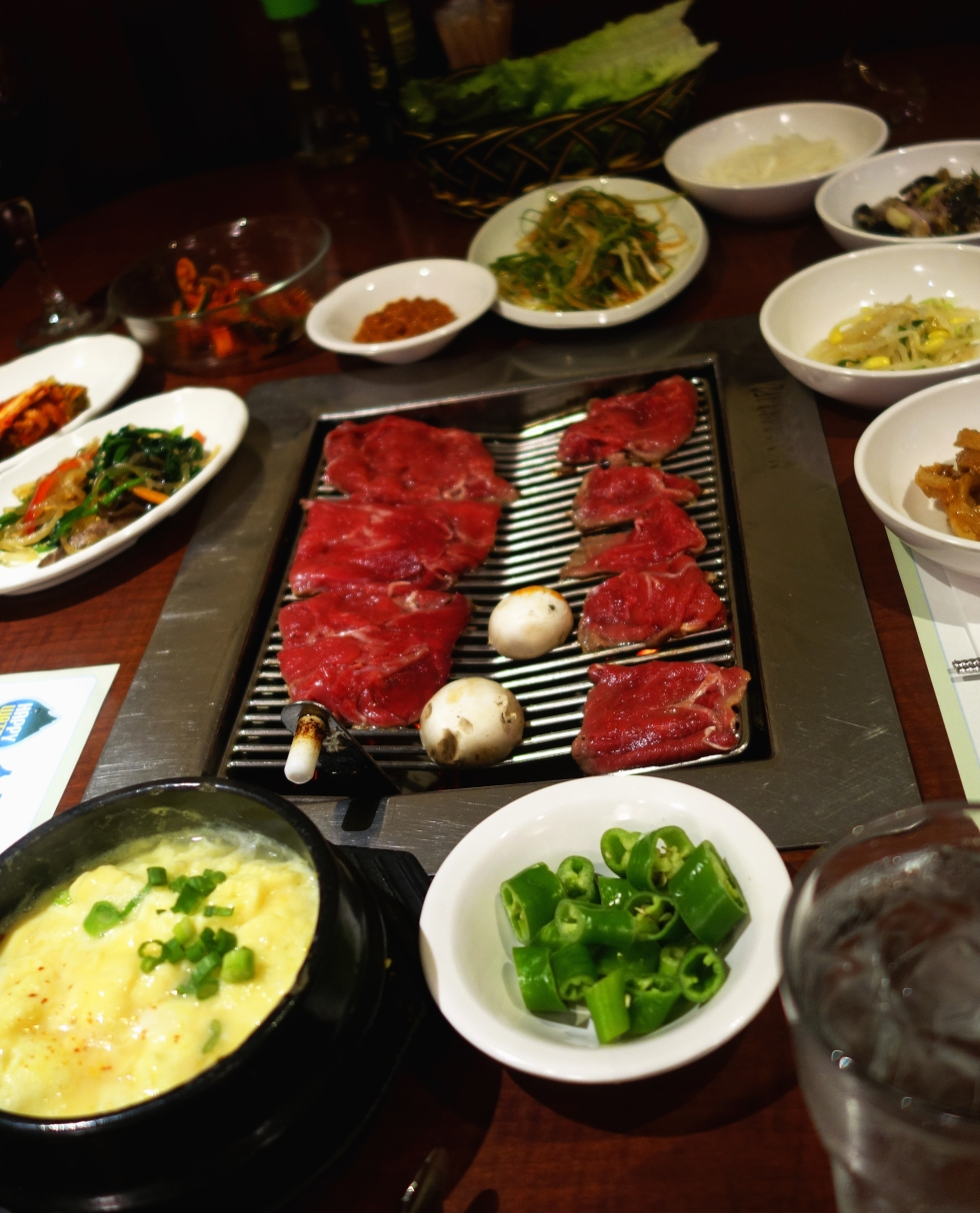 So Moon Nan Jip – Korean BBQ - Palisades Park NJ - Bulgogi just placed on the grill, all of our sides and of course my fave - steamed egg. YUM