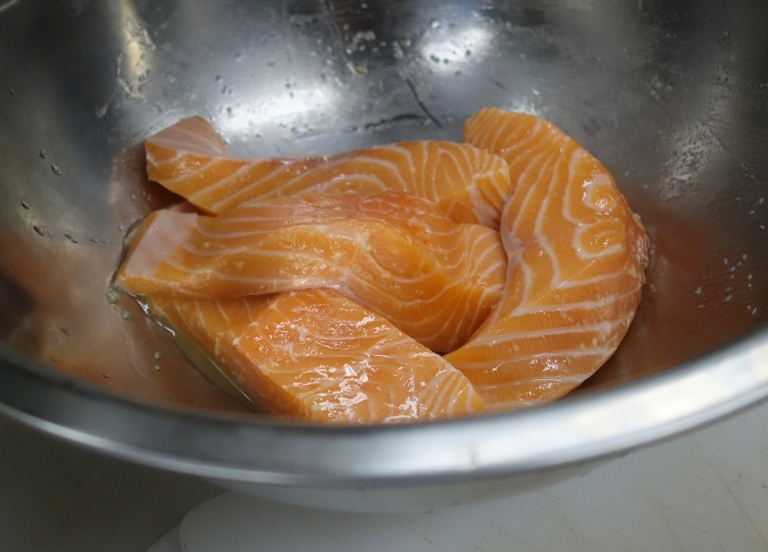 Salmon marinates in olive oil, chopped garlic -which they soak for days in olive oil, and kosher salt.