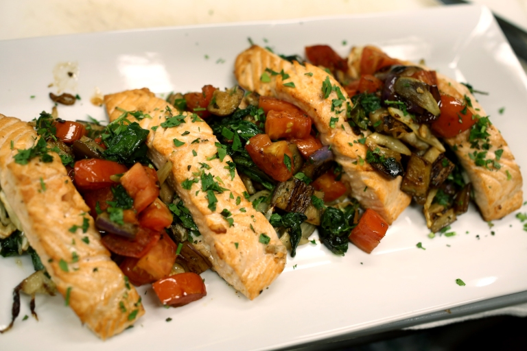 The stuffed salmon is plated and topped with the sautéed eggplant and tomato and garnished with fresh herbs.
