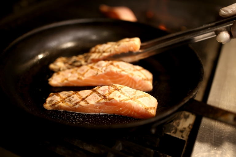 The grilled salmon is transferred to a pan, which has been sprayed lightly with pam, to bake in the oven for 13 minutes at 350 degrees.