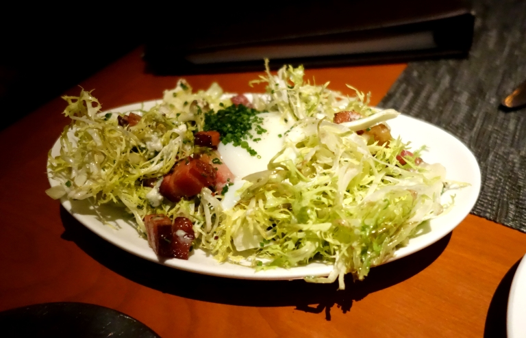 Warm frisée salad topped with a poached farm egg, smoked bacon lardons and dressed in a champagne vinaigrette. YUM.